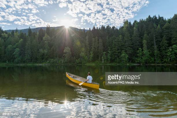 Man paddles canoe across mountain lake, sunrise