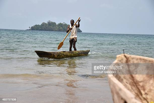 A man paddles his dugout off Arena Blaca beach near Luba in Equatorial Guinea on January 31 2015 AFP PHOTO / ISSOUF SANOGO