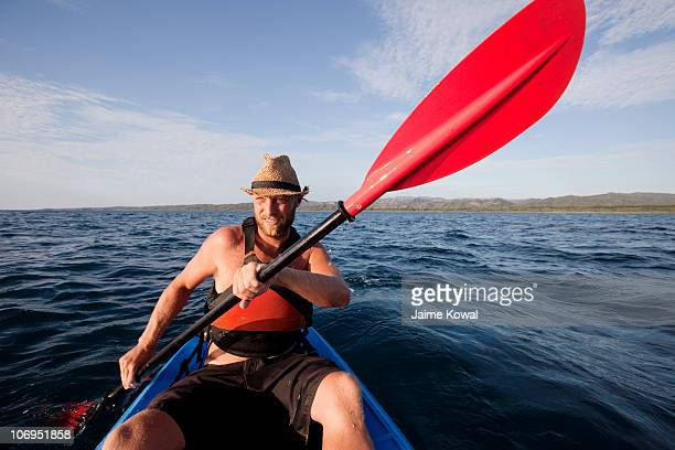 man paddles his ocean kayak on open water - guanacaste stock pictures, royalty-free photos & images