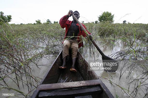A man paddles in a canoe across hios family's inundated fields 23 September 2007 near the village of Nasia in northern Ghana after the Volta Blanc...