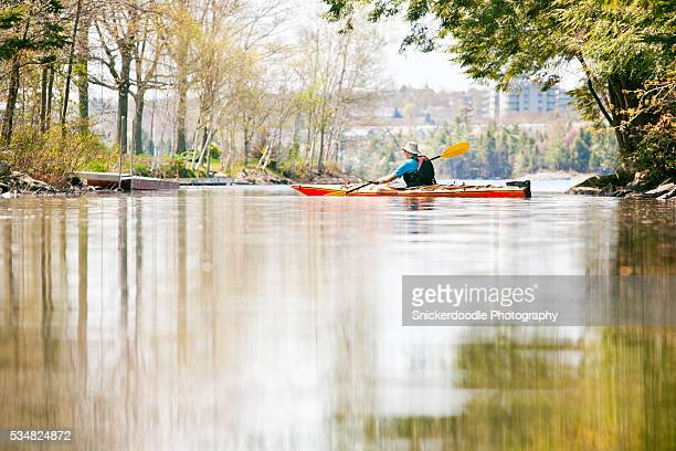 man paddles kayak in tranquil water - snickerdoodle stock pictures, royalty-free photos & images