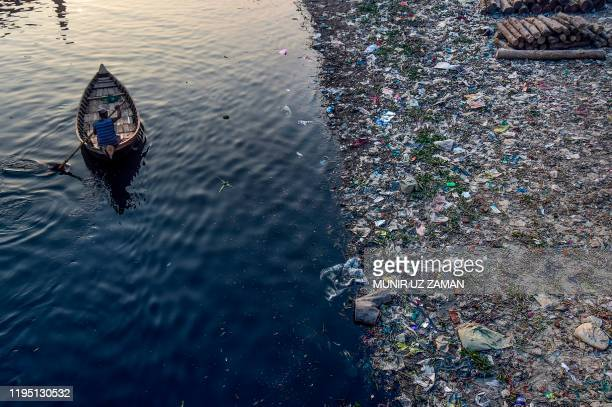 Man paddles on a boat as plastic bags float on the water surface of the Buriganga river in Dhaka on January 21, 2020. - Bangladesh's high court has...