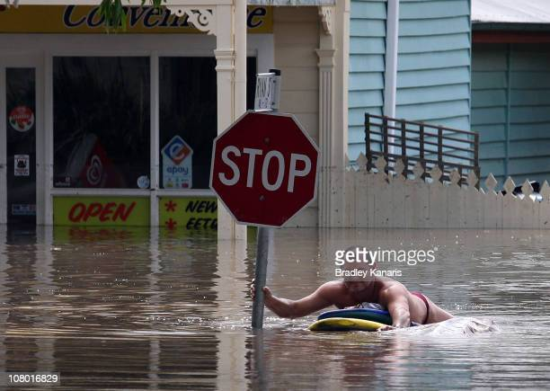 A man paddles on his surf board down Hoogley Street in the suburb of West End on January 13 2011 in Brisbane Australia The Brisbane river peaked at...