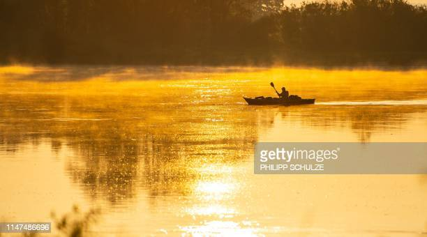 A man paddles on the river Elbe as sun rises in Neu Darchau near Lueneburg northern Germany on June 2 2019 / Germany OUT