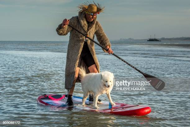 A man paddles with his dog on a surf board as people take part in the traditional New Year's sea plunge on January 1 2016 at MaloLesBains beach in...