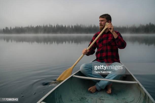 man paddling a canoe in montana on a foggy lake - チェックシャツ ストックフォトと画像