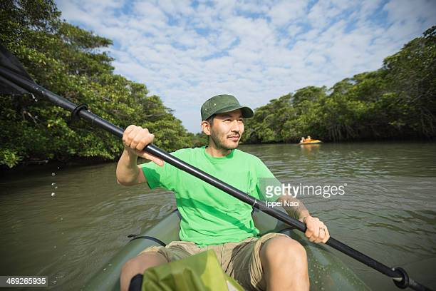 Man paddling a kayak on mangrove river