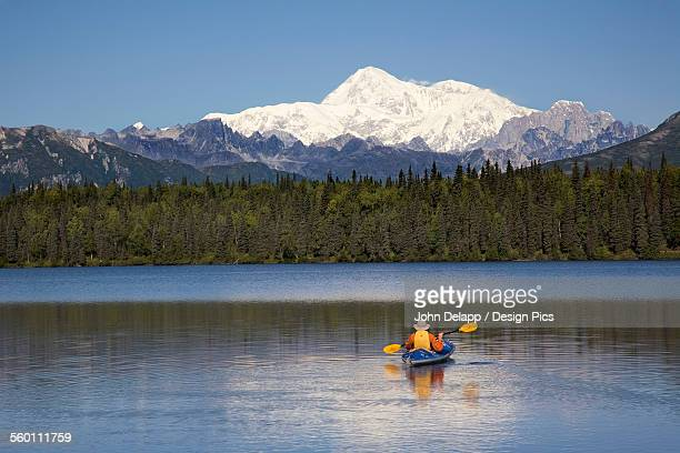 Man Paddling A Klepper Kayak On Byers Lake At Denali State Park. Mt. Mckinley Is Visible In The Background. August. Summer In The Interio Of Alaska.