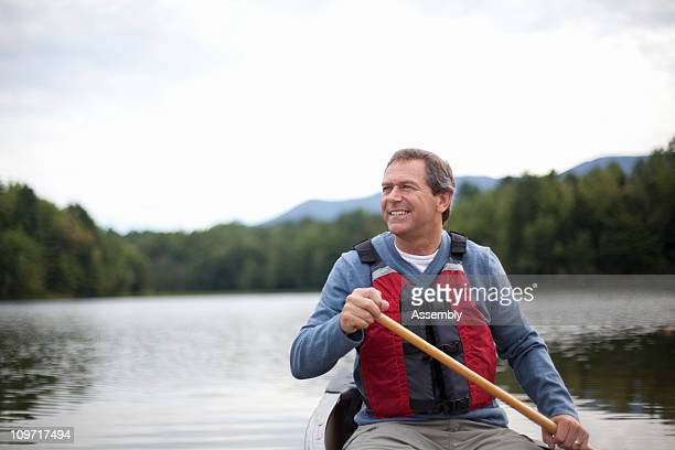Man paddling canoe on tranquil lake