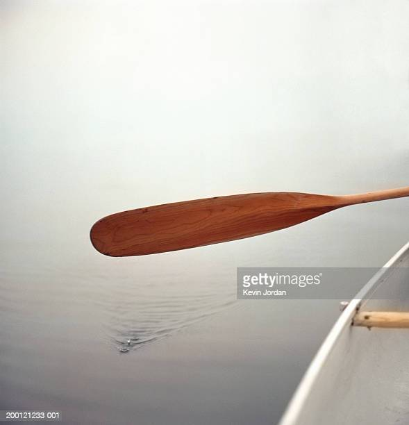 Man paddling in canoe, close-up of oar above water