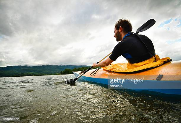Man paddling in wooden kayak