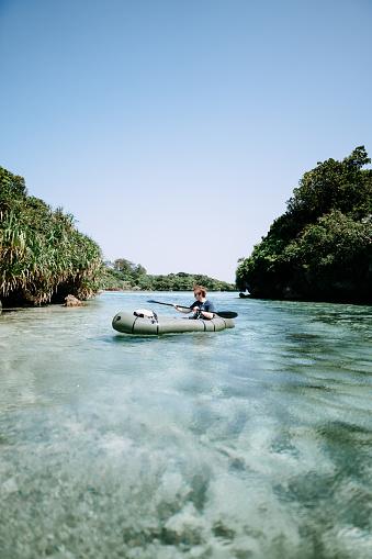 Man paddling inflatable raft on clear tropical water, Ishigaki Island, Okinawa, Japan - gettyimageskorea