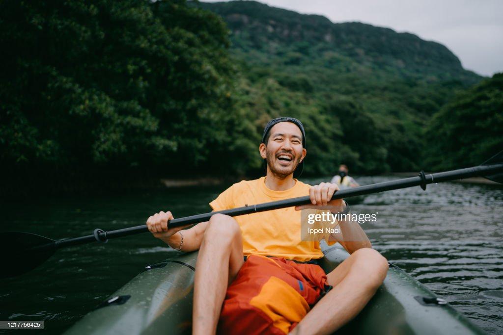 Man paddling kayak in mangrove river and laughing, Iriomote, Japan : Stock Photo