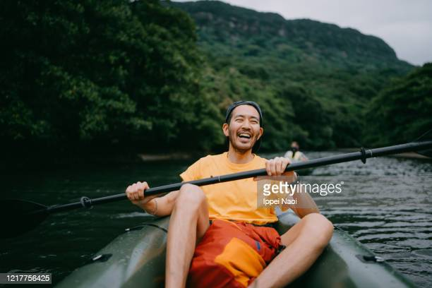 man paddling kayak in mangrove river and laughing, iriomote, japan - active lifestyle stock pictures, royalty-free photos & images