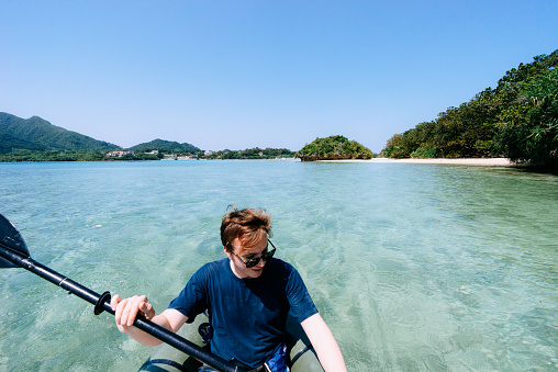 Man paddling kayak on clear tropical water, Okinawa, Japan - gettyimageskorea