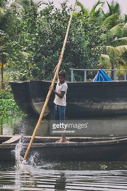 Man paddling Kettuvallam on the Kerala Backwaters in India
