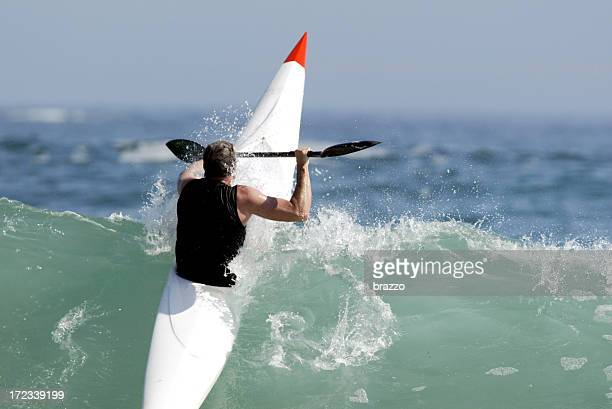 Man paddling over wave in white and red sea kayak
