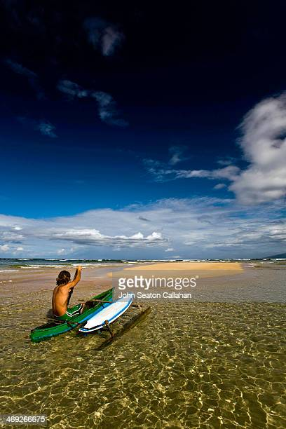 Man paddling pirogue with surfboard