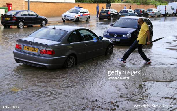 CONTENT] Man paddling through water in a London street following a burst water main