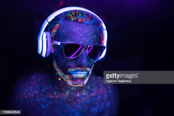 man painted in fluorescent uv colors with sunglasses and headset - fluorescent light stock pictures, royalty-free photos & images