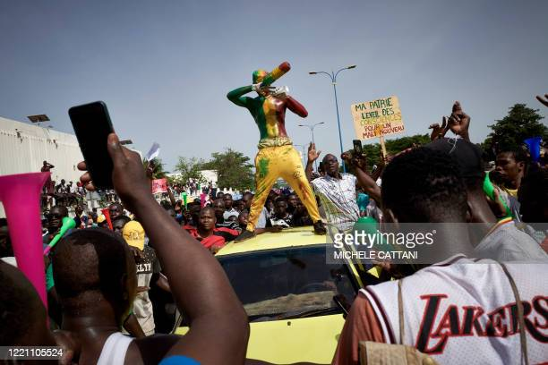 A man painted in the colours of Malian flag gestures at Independance square as protesters gather to demand that Malian President Ibrahim Boubacar...