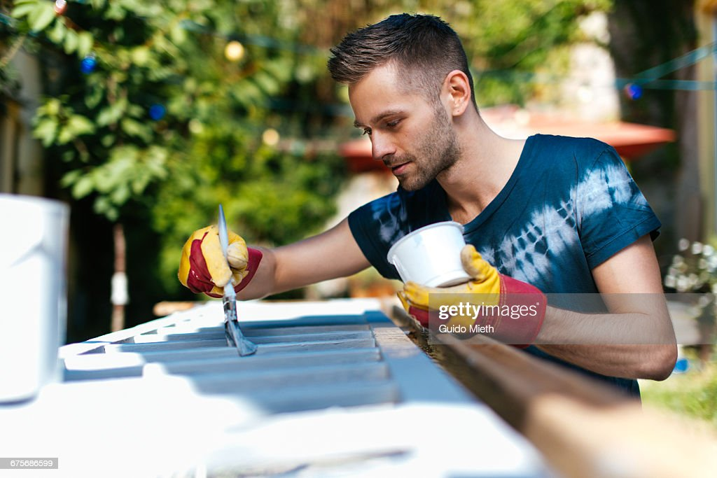 Man painting a bannister outdoor. : Stock-Foto