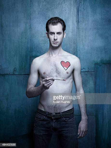 Man painting a heart onto his chest