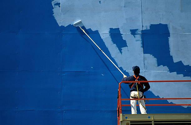 Man painting billboard