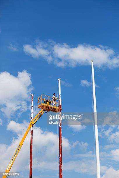 Man painting flagpoles from platform