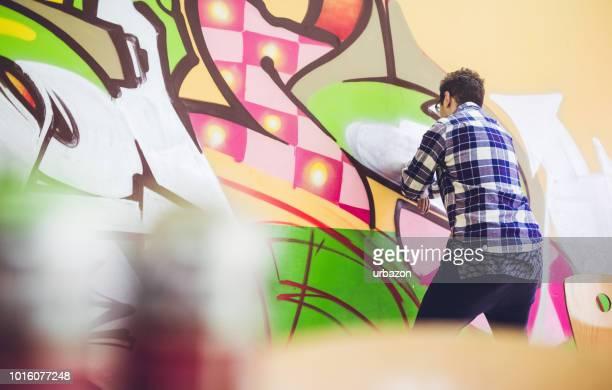 オレンジ色の壁に男絵の落書き - 壁画 ストックフォトと画像