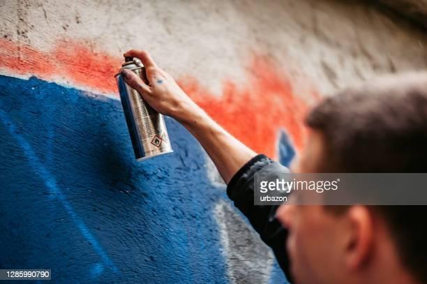 hombre pintando grafitis en la pared - graffiti fotografías e imágenes de stock