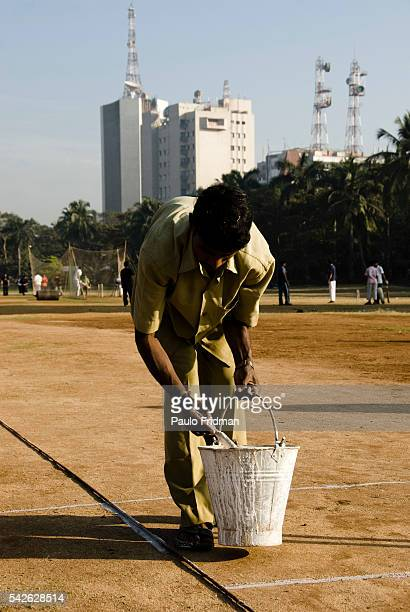 Man painting lines in a cricket field in Mumbai Maharastra India