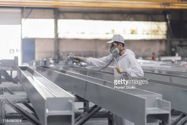 man painting metal in factory - respirator mask stock pictures, royalty-free photos & images