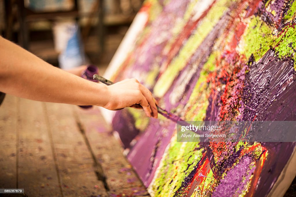 Man painting on canvas in studio : Stock Photo