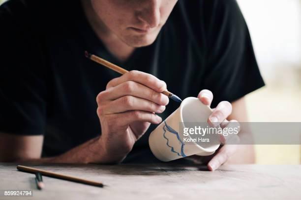 Man painting on ceramic work