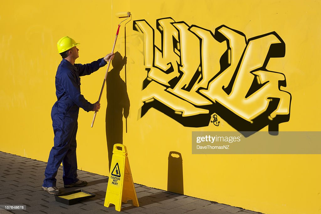 Man Painting Over Graffiti On A Yellow Wall Stock Photo | Getty Images