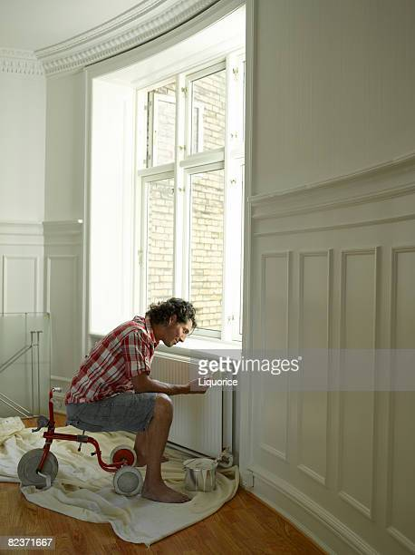 man painting radiator