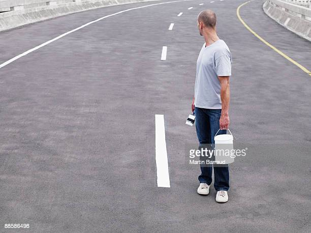 Man painting road lane divider
