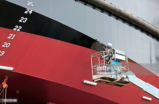 man painting ship's hull with roller - ship stock pictures, royalty-free photos & images