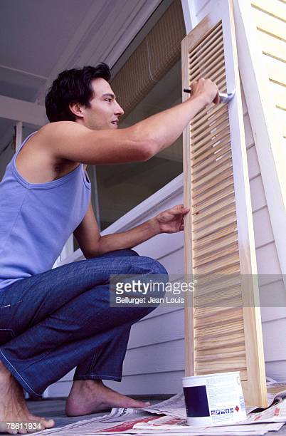 Man painting shutter