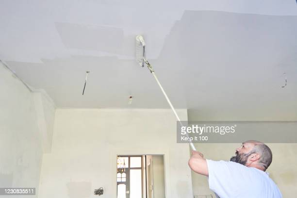 man painting the ceiling of a room - ceiling stock pictures, royalty-free photos & images