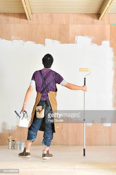 Man painting wall, rear view
