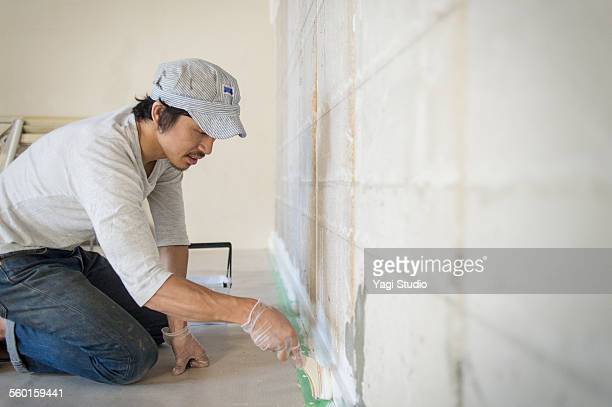 Man painting wall with brush