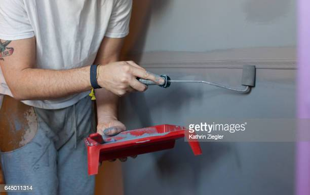 Man painting wall with gray color, using small paint roller