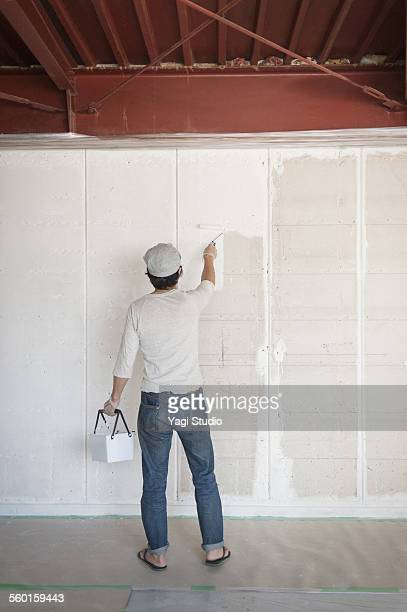 Man painting wall with roller brush