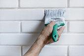 man painting with brush brick wall