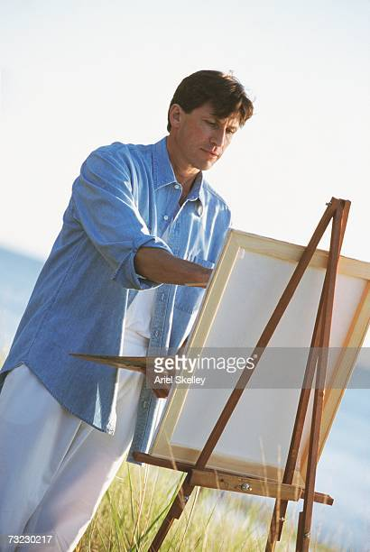Man painting with easel outdoors