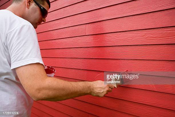 Man painting wood exterior with red paint