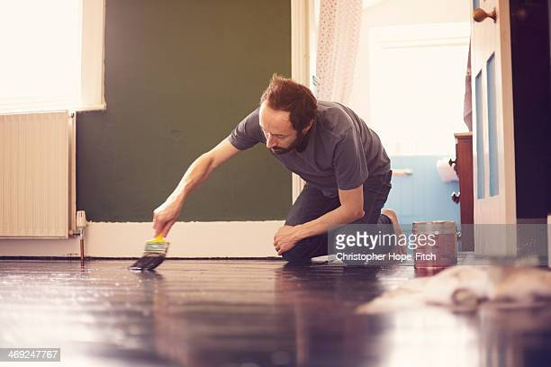 man painting wooden floor - kneeling stock pictures, royalty-free photos & images