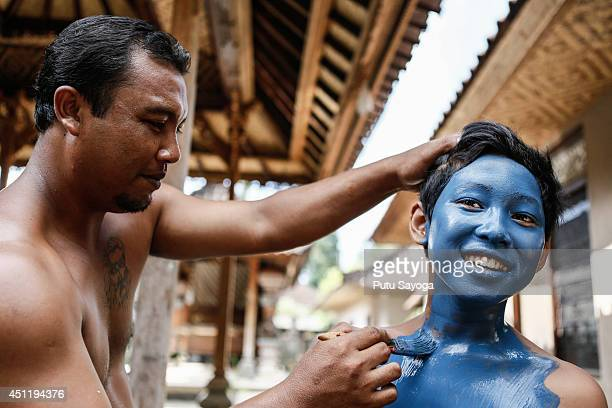 A man paints a boy's body in preparation for the Grebeg ritual on June 25 2014 in Tegallalang Village Gianyar Bali Indonesia During the biannual...